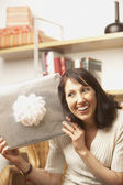 Woman holding up gift — Stock Photo