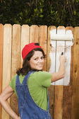 Woman painting fence — Stock Photo