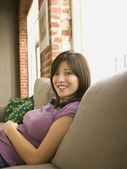 Young woman sitting on a couch — Stock Photo