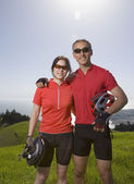 Asian couple wearing bicycle gear in countryside — Stock Photo