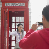 Man taking photograph of Asian woman next to public telephone box in London — Стоковое фото