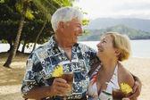 Senior pareja sonriendo el uno al otro en escena tropical — Foto de Stock