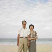Couple standing arm in arm at beach — Stock Photo