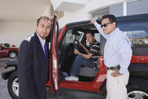Hispanic father and son at car dealership — Stock Photo