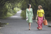 Two women walking on a road — Стоковое фото