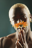 Young man smelling orange flower — Stock Photo