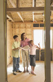 Family with blueprints on construction site — Stock Photo