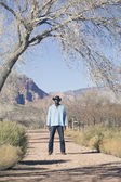 Young man in cowboy outfit standing on a dirt path — Stock Photo