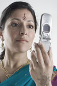 Young woman in traditional Indian dress holding cell phone — Stock Photo