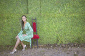 Young woman sitting in front of hedge — Stock Photo