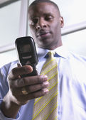Low angle view of African businessman using cell phone — Stock Photo