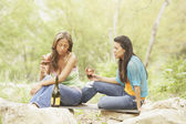 Two young women holding glasses of wine — Stock Photo