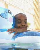 Young boy playing in an innertube in a swimming pool — Stock Photo