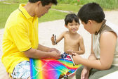 Father and sons flying kite — Stock Photo