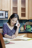 Woman writing while talking on phone — Foto Stock
