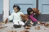 Girls collecting fall leaves — Stock Photo