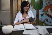 Businesswoman petting a cat at her desk — Stock Photo