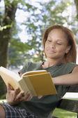 африканская женщина, чтение на скамейке в парке — Стоковое фото