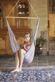 Young woman sitting on swing — Stock Photo