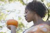 Low angle portrait of woman holding pumpkin — Stock Photo