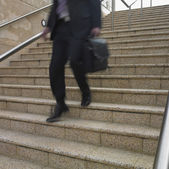 Blurred view of businessman's legs descending stairs — Stock Photo
