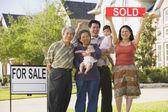 Familia asiática multigeneracional sosteniendo un cartel vendido en frente de casa — Foto de Stock