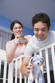 Couple Leaning into Baby Bed Taking Pictures — Stock Photo