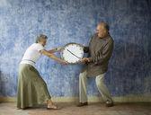 Multi-ethnic senior couple having tug of war with clock — Stock Photo