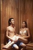 Pareja hispana sentado en sauna — Foto de Stock