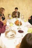 Hispanic family saying grace at dinner table — Stock Photo