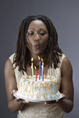 Woman blowing out candles on birthday cake — Stock Photo