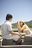 Mujer joven fotografiando a su novio en un convertible — Foto de Stock