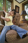Young girl sitting in chair — Stock Photo