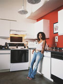 Young woman relaxing in kitchen — Stock Photo