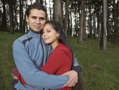 Portrait of couple hugging in forest — Stock Photo
