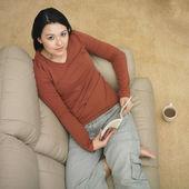Karışık ırk kadın kanepe üzerinde okuma — Stok fotoğraf