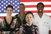 Multi-ethnic standing in front of American flag — Stock Photo