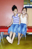 Sisters on bench laughing — Stock Photo