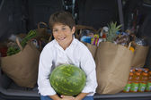 Boy holding watermelon next to bags of groceries — Stock Photo