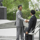 Two businessmen shaking hands on stairs outdoors — Photo
