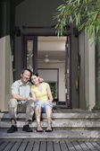 Portrait of father and daughter sitting on front steps — Stock Photo
