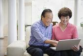 Senior Asian couple looking at laptop — Stock Photo
