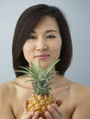 Asian woman holding pineapple — Stock Photo