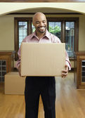 Young man carrying a box — Stock Photo
