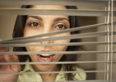 Portrait of businesswoman peering through blinds — Stock Photo