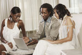 Multi-ethnic friends looking at laptop — Stock Photo
