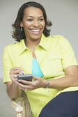 Woman holding a handheld device — Stock Photo