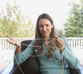 Portrait of woman with tangled knitting — Stock Photo