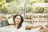 Portrait of young woman lying on hammock — Stock Photo