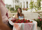 Mature woman holding basket of strawberries — Stock Photo